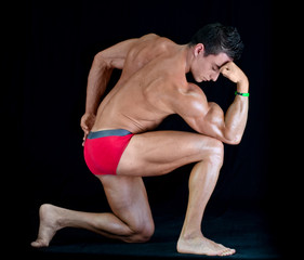 Attractiave young muscle man in classic pose on his knee