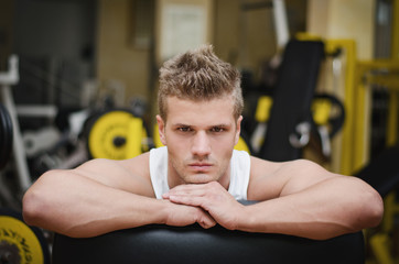 Attractive young athletic man resting on gym equipment