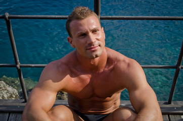 Handsome young muscle man sitting with sea behind