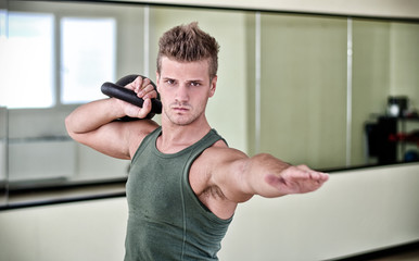 Handsome young man exercising with kettlebell in gym