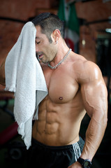 Muscular bodybuilder drying his face after workout in a gym
