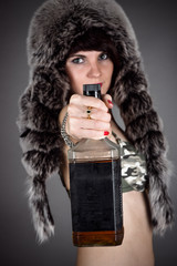woman in a fur hat holds out a bottle of whiskey