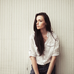 beautiful girl in a white shirt against the wall