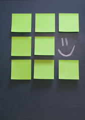 Green Post-it notes at blackboard.