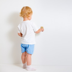 Baby boy with paint brush rear view standing near blank white wa