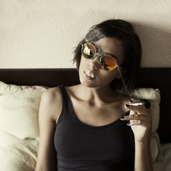 beautiful girl with round glasses hipster smokes in bed