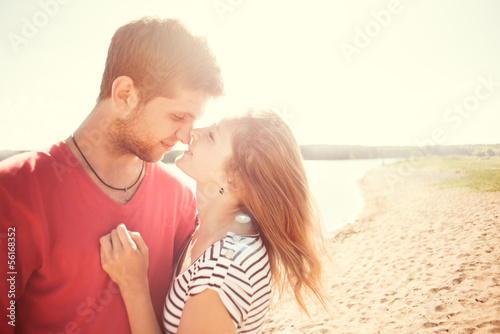 beautiful couple kissing on the beach on a sunny morning