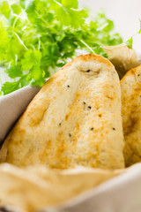 Naan breads in basket with cilantro (coriander)