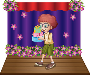 A stage with a young boy holding gifts