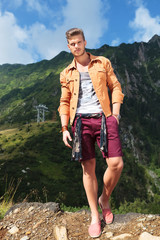 casual man in the mountains with hand in pocket
