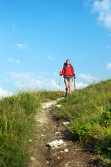 Smiling hiking young woman with backpack