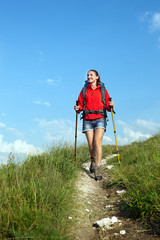 Smiling hiking young woman with backpack and trekking poles