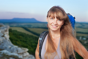 Smiling young woman with backpack in the mountains