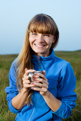 Smiling young woman with cup outdoor