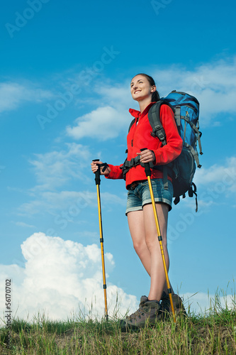 Smiling hiking young woman  standing on a green meadow