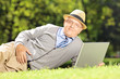 Senior man with hat lying on a grass working on a laptop in park