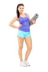Full length portrait of a female athlete  listening music and ho
