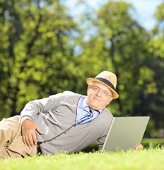 Senior man with hat lying on a green grass and working on a lapt