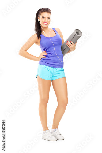 Full length portrait of a female athlete  listening music and ho