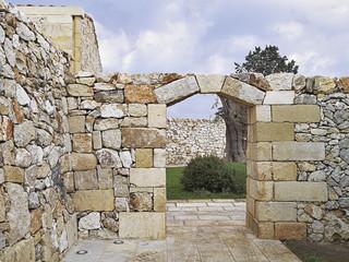 portale in pietra con chiave di volta e muro di pietra
