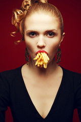 Unhealthy eating. Junk food concept. Girl eating potato fries