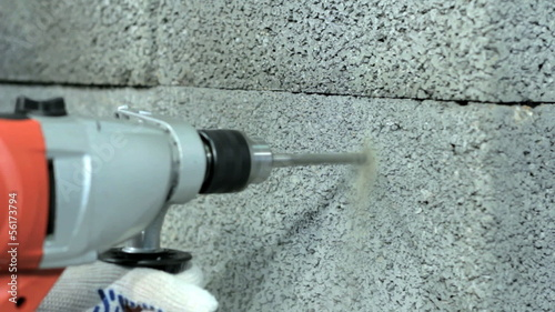 Drilling hole into concrete wall.