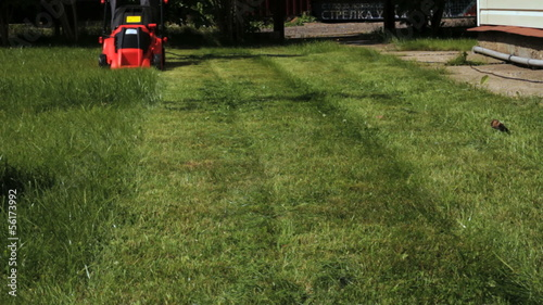 Garden worker cutting overgrown grass with lawn mower weeding ma