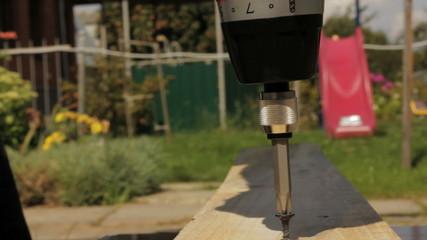 Electric screwdriver screwing screw in wood.