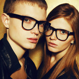 Portrait of gorgeous red-haired fashion twins in black glasses