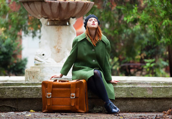 Redhead girl with suitcase sitting at autumn outdoor.