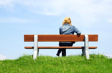 Frau auf Sitzbank in der Natur