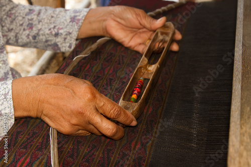 Woman working at Thai traditional loom with wooden bobbin