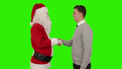 Santa Claus and Young Businessman shaking hands, Green Screen