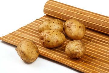 tubers of potatoes on the mat