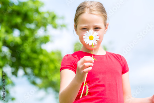 Girl with buttercups in summer outdoors