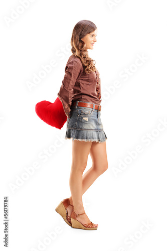 Young female holding a red heart behind her back