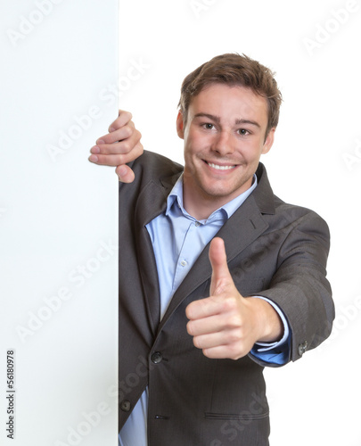 Young businessman showing thumb behind a signboard