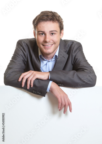 Young businessman behind a signboard