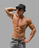 Handsome young man naked, wearing only jeans and hat
