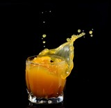 splashing out of a glass with juice on a black background
