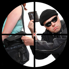 Thief stealing from handbag in a police sniper's scope.