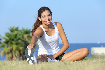 Beautiful fitness woman stretching outdoor on the grass