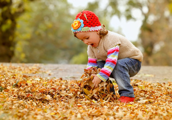 Cute child playing with autumn leaves
