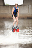 Young man using flyboard machine on river