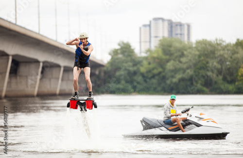 Young man on flyboard pretending taking picture, humorous aspect