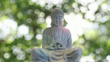 Bronze Buddha in Meditation Pose on Bokeh Background
