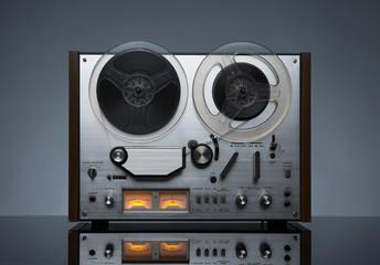 Vintage working analog recorder reel to reel on dark background