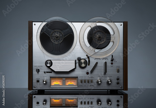 Vintage working analog recorder reel to reel on dark background
