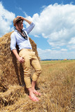 side view of a casual man in a hay field