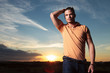 casual man passing hand through hair at sunset